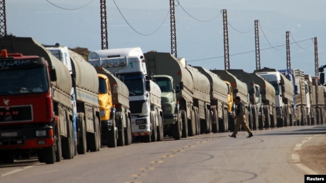 Trucks park at the Lebanese-Syrian border after residents in Lebanon blocked the road to protest what they said were shipments of diesel fuel to the Syrian government February 13, 2013.