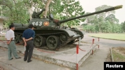 FILE - Tourists in Ho Chi Minh City look at a Soviet-made tank.