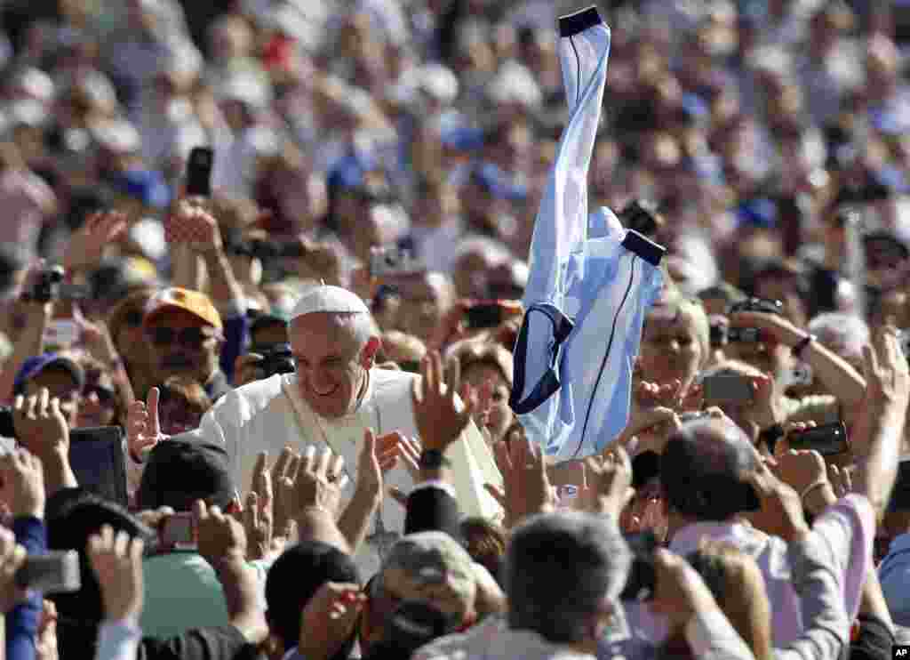 A faithful tosses in the air a jersey with the colors of the Argentine flag as Pope Francis greets faithful upon arrival for his weekly general audience in St. Peter's Square at the Vatican.