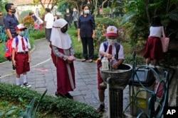 Siswa mengenakan masker dan mencuci tangan sebelum memasuki gedung sekolah pada hari pertama pembukaan kembali pembelajaran tatap muka di Jakarta, Senin, 30 Agustus 2021.