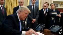 川普总统在白宫椭圆形办公室签署行政令。(2017年1月23日)