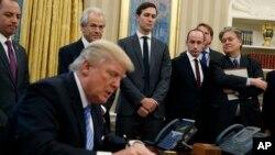 """Presiden AS Donald Trump menandatangani perintah eksekutif """"Mexico City Policy"""" di Gedung Putih (23/1) disaksikan pejabat terdekat. (AP/Evan Vucci)"""