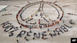 "FILE - Environmental activists form human chains representing the peace sign and spelling out ""100% renewable,"" on the sidelines of the 2015 Paris Climate Summit, near the Eiffel Tower in Paris, France, Dec. 6, 2015."