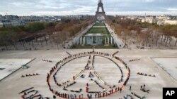 """在巴黎氣候峰會之際,環保人士在巴黎組成和平圖標和""""100%可再生""""的口號(2015年12月6日)"""