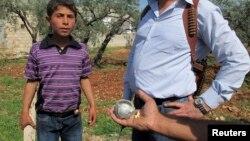 Seorang pria memegang bom rumpun dalam pencarian oleh warga dan Tentara Pembebasan Suriah di Idlib, Suriah. (Foto: Dok)