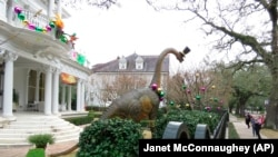 People walk by dinosaurs in front of a mansion on St. Charles Avenue in New Orleans, on Tuesday, Jan. 26, 2021 (AP Photo/Janet McConnaughey)