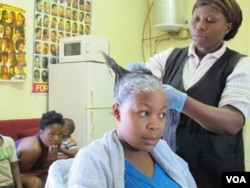 Rita Dantaa, who owns a hair salon in downtown Johannesburg, applies relaxer to her client's hair, May 16, 2014 (Gillian Parker for VOA).