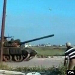Seorang demonstran anti pemerintah melemparkan batu ke arah tank militer Suriah.