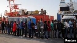 Migranti steej u redu dok im pomažu aktivisti španskog Crvenog krsta nakon što su ih spasilački brodovi dovezli u luku Algeciras, južna Španija, 22. jula 2018.