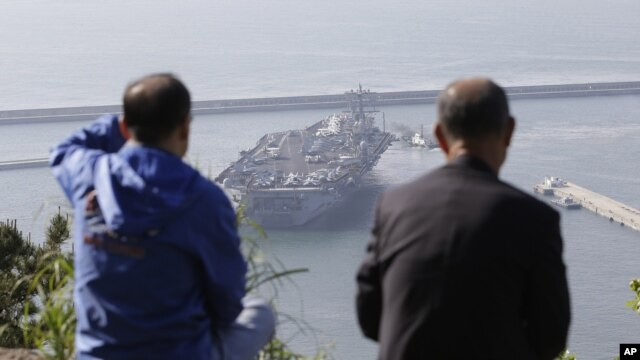 South Koreans on a hilltop park watch the U.S. nuclear-powered aircraft carrier USS Nimitz at Busan port, south of Seoul, South Korea, May 11, 2013.