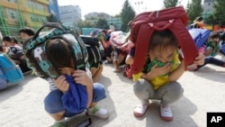 Elementary school students, with schoolbags on their heads, take shelter on the ground during an earthquake drill at Songjung Elementary School in Seoul, South Korea, Sept. 23, 2016.
