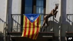 A mannequin stands next to a ''estelada'' or Catalonia independence flag, on a balcony, in Barcelona, Spain, Oct. 23, 2017.