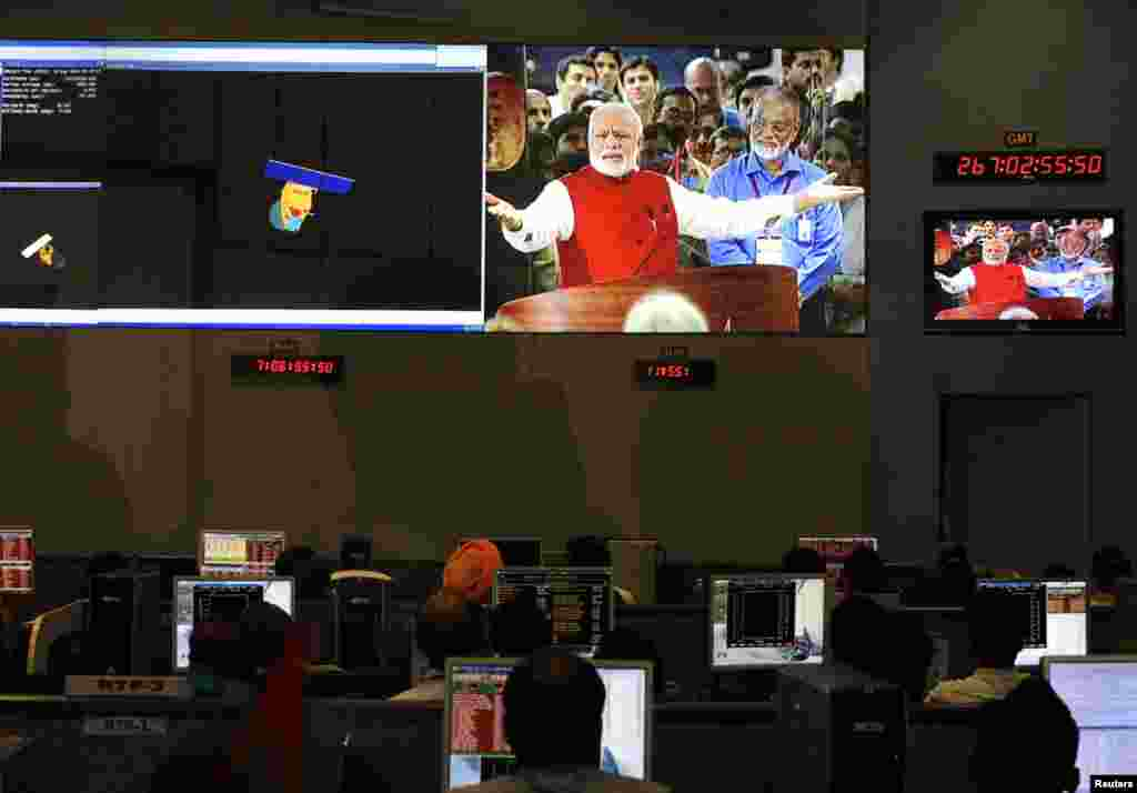Indian Space Research Organization scientists and engineers watch Prime Minister Narendra Modi on screens after India's satellite successfully entered Mars' orbit, at the Spacecraft Control Center, in the southern Indian city of Bangalore, Sept. 24, 2014.