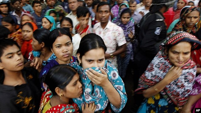 People look at a burnt garment factory outside Dhaka, Bangladesh, November 25, 2012.