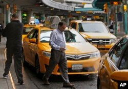 A taxi driver heads to his vehicle as other taxis line up outside LaGuardia Airport in New York.