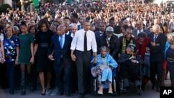 """Presiden AS Barack Obama (tengah) bergandengan tangan dengan Amelia Boynton Robinson, yang dipukuli dalam tragedi """"Minggu Berdarah"""" dalam peringatan 50 tahun pawai hak sipil di Selma, Alabama (7/3). (AP/Jacquelyn Martin)"""