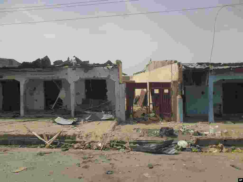 Heavily damaged buildings and bloodstains on the street can be seen following a suicide bomb explosion at a World Cup viewing center, Damaturu, Nigeria, June 18, 2014.