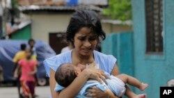 Une sri-lankaise s'éloigne du sanctuaire de St. Anthony, tenant son bébé après que la police a découvert des engins explosifs dans un véhicule garé à Colombo, au Sri Lanka, le lundi 22 avril 2019.