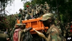 FILE - M23 rebels sit in a vehicle as they withdraw from the eastern Congo town of Goma, Dec. 2012.