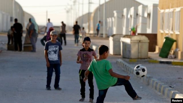 Syrian refugee children play with a soccer ball at the Mrajeeb Al Fhood refugee camp in Zarqa, Jordan, July 1, 2014.
