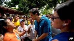 Opposition candidate Carlos Ocariz, who is running for governor of Miranda state, speaks with a woman as he campaigns in Guarenas, on the outskirts of Caracas, Venezuela, Oct. 7, 2017.