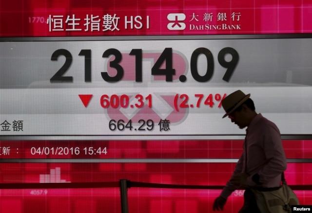 A man walks past a panel displaying the benchmark Hang Seng index during afternoon trading in Hong Kong, China, Jan. 4, 2016.