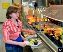Clara Zonis, front, and Kelsey Hiscock select food items from the lunch line of the cafeteria at Draper Middle School in Rotterdam, N.Y. (AP Photo/Hans Pennink, File)
