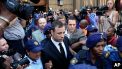 FILE: Escorted by police and security, Oscar Pistorius leaves the court in Pretoria, South Africa, Sept. 12, 2014.