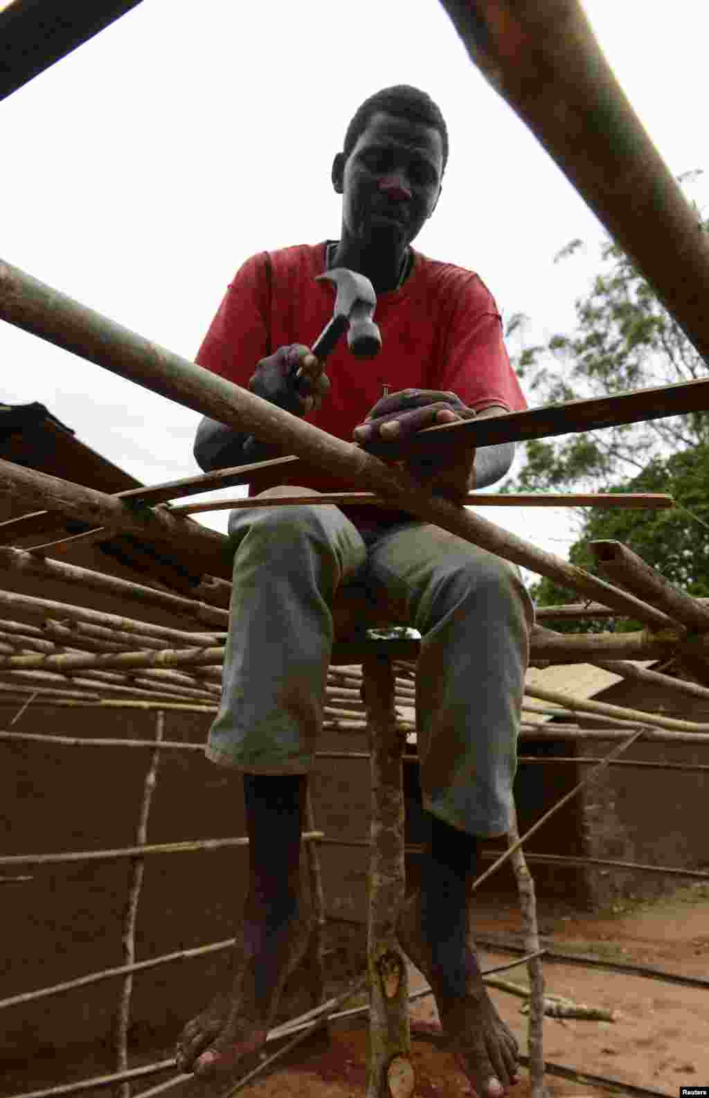 A man works on building a makeshift voting station near Gorongosa, central Mozambique, Nov. 19, 2013.