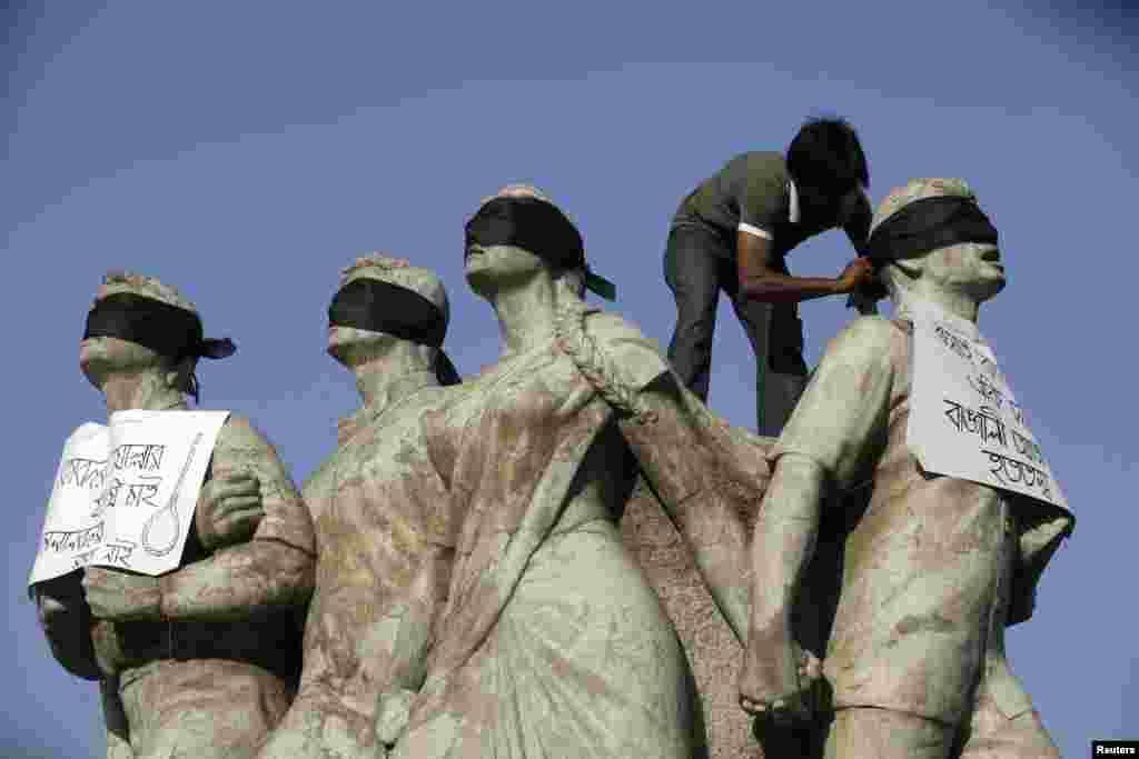 Seorang aktivis mahasiswa menempatkan syal hitam pada mata Shoparjito Shadhinota, sebuah patung yang mewakili bagian-bagian dari masyarakat Bangladesh pada perang kemerdekaan negara tersebut pada tahun 1971, di kampus Universitas Dhaka. Mahasiswa menuntut hukuman mati untuk Jamaat-e-Islami, pemimpin senior Abdul Quade. Pengadilan kejahatan perang menjatuhkankan kepadanya hukuman penjara seumur hidup.