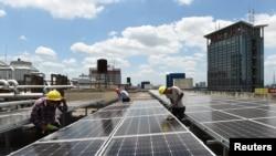 在中国浙江省义乌市国际商贸城的屋顶,工人安装太阳能电池板(2017年7月17日)。