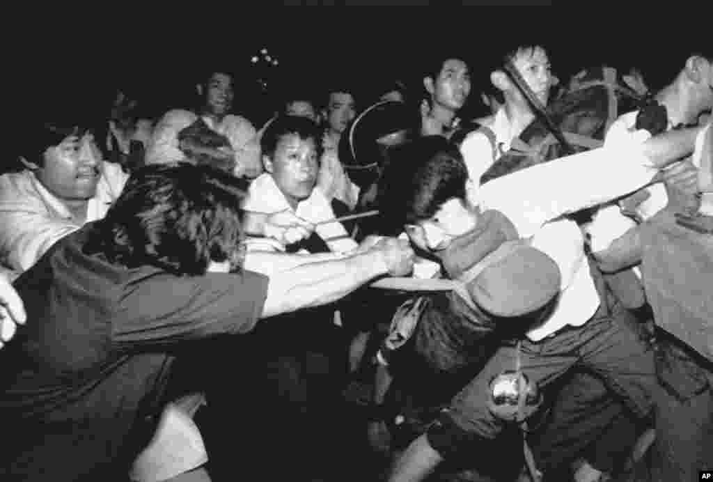 A man tries to pull a Chinese soldier away from his comrades as thousands of Beijing citizens turned out to block thousands of troops on their way towards Tiananmen Square, June 3, 1989.