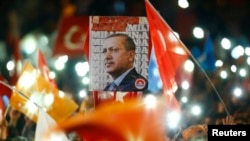 People wave flags and hold a portrait of Turkish President Recep Tayyip Erdogan as they celebrate the ruling AK Party's election win, in Ankara, Turkey Nov. 2, 2015.