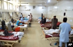 Injured men receive treatment at a hospital following a suicide attack in the city of Jalalabad, east of Kabul, June 11, 2018.