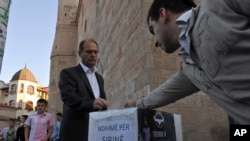 "FILE - Kosovo Muslims donate money in a box labeled ""Help for Syria"" in front of the Grand Mosque in Kosovo's capital Pristina in this 2012."