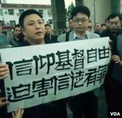 律师程建刚(译音)在中国山东省菏泽市曹县法院外面展示标语 (对华援助新闻网图片)