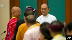 Myanmar President Thein Sein, rear right, shakes hands with leaders of armed ethnic groups during a meeting for the Nationwide Ceasefire Agreement (NCA) between representatives of the Myanmar government and leaders of armed ethnic groups in Naypyidaw, Mya