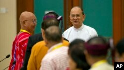 Myanmar President Thein Sein, rear right, shakes hands with leaders of armed ethnic groups during a meeting for the Nationwide Cease-fire Agreement (NCA) between representatives of the Myanmar government and leaders of armed ethnic groups in Naypyidaw, Sept. 9, 2015.