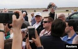 El presidente de EE.UU. Donald Trump levanta una gorra de camuflaje al llegar al aeropuerto internacional McAllen, en McAllen, Texas, en la frontera con México, el jueves 10 de enero de 2019.