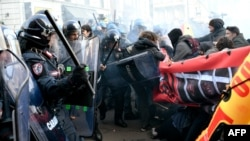 Police clash with demonstrators during an anti-fascist and anti-racist march to protest against a Lega far-right party general election campaign rally in Milan, Italy, Feb. 24, 2018.