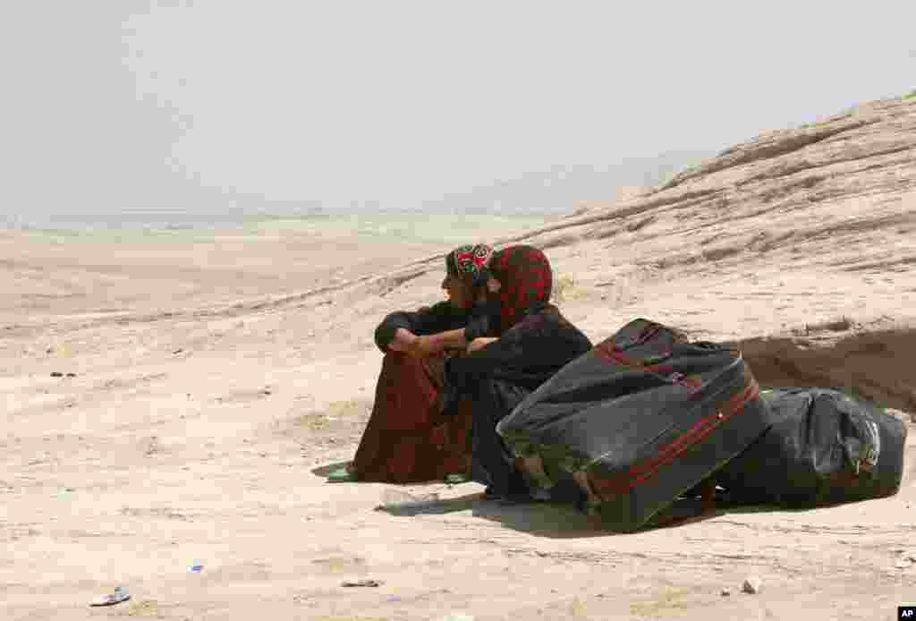 Syrian refugees take a rest as they cross into Iraq at the Peshkhabour border point in Dahuk, August 20, 2013.