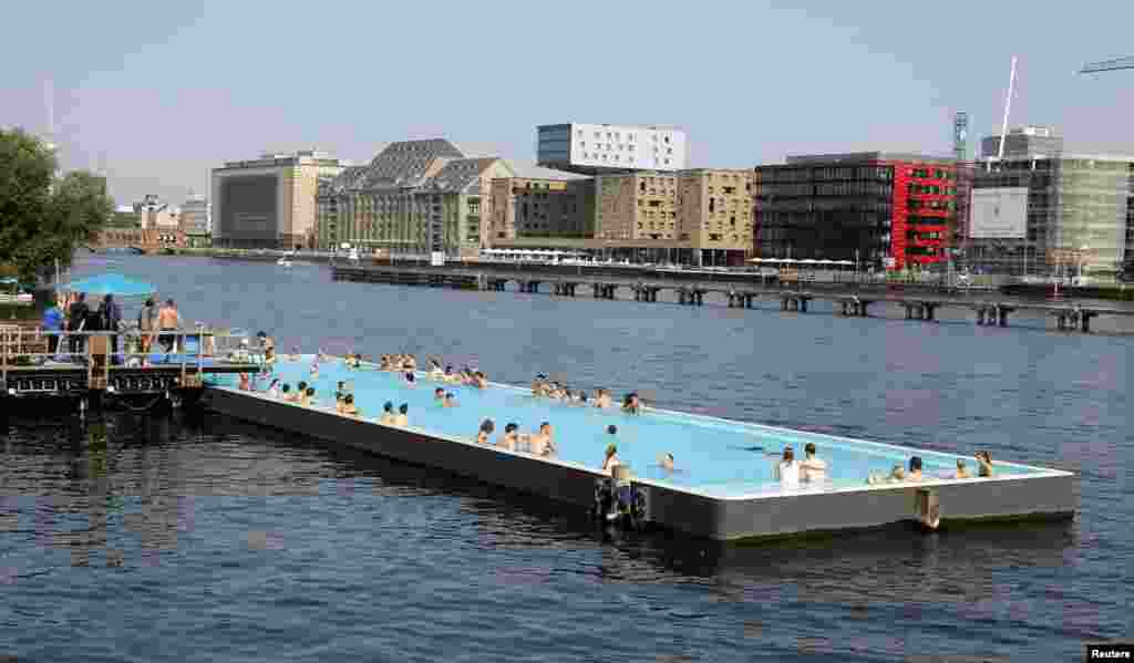 People swim in a floating swimming pool anchored on the bank of the Spree River in Berlin, Germany.