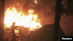 Riot police set fire to tents pitched by anti-Mursi demonstrators at Tahrir Square in Cairo January 25, 2013.