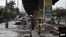 Cảnh sát hướng dẫn giao thông trên con đường bị ngập ở ngoại ô thành phố Makati, phía đông Manila, Philippines, ngày 8/5/2011