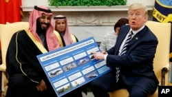 President Donald Trump shows a chart highlighting arms sales to Saudi Arabia during a meeting with Saudi Crown Prince Mohammed bin Salman in the Oval Office of the White House, March 20, 2018, in Washington.