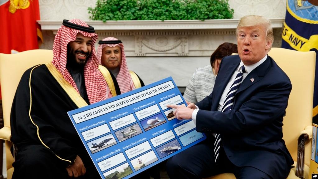 Tổng thống Donald Trump cho xem một tấm bảng minh họa những thương vụ vũ khí với Ả-rập Xê-út trong một cuộc hội kiến Thái tử Mohammed bin Salman trong Phòng Bầu dục của Nhà Trắng, ngày 20 tháng 3, 2018, ở Washington.