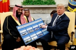 President Donald Trump shows a chart highlighting arms sales to Saudi Arabia during a meeting with Saudi Crown Prince Mohammed bin Salman in the Oval Office of the White House, Tuesday, March 20, 2018, in Washington.