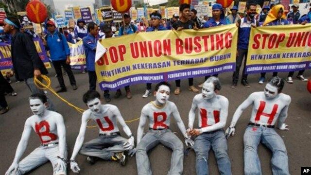Para pekerja mencat wajah dan tubuhnya dalam aksi demonstrasi memperingati Hari Buruh Sedunia di Jakarta, Rabu (1/5). (AP/Achmad Ibrahim)