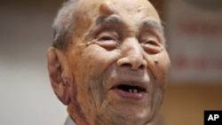 Yasutaro Koide, the 112-year-old living in the central Japanese city of Nagoya, smiles upon being formally recognized as the world's oldest man by the Guinness World Records at a nursing home in Nagoya, Aug. 21, 2015.
