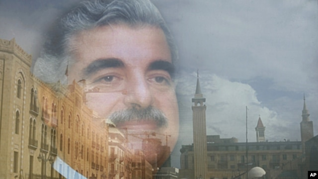 The buildings of Beirut's downtown are seen reflected on a portrait of the slain former Lebanese Prime Minister Rafik Hariri, in Beirut. (file photo)
